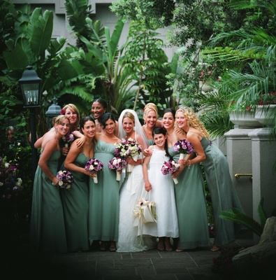 Eight bridesmaids outside with bride and flower girl