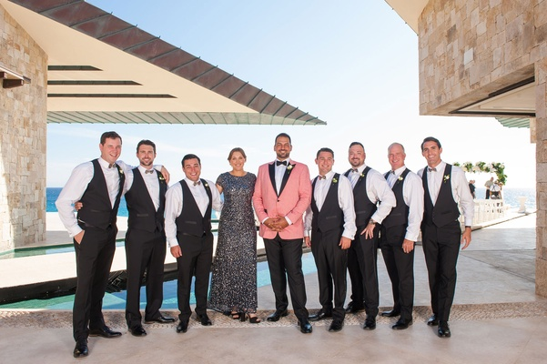 groom in salmon tuxedo jacket, groomsmen in suit vests, groomswoman in black/grey sequin gown