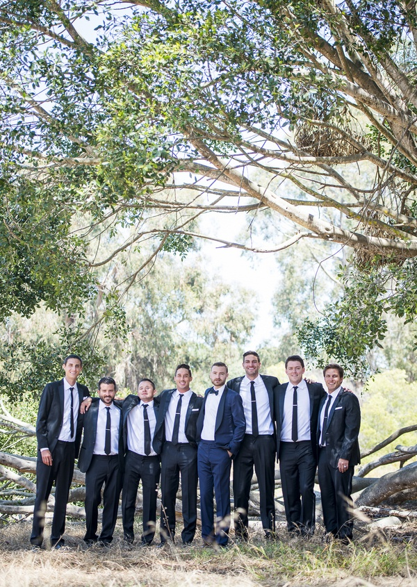 groom navy blue tuxedo groomsmen black tuxedos stand together in forest in santa barbara