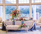 lounge seating at wedding dining table tufted bench with bright boho blooms