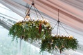 tent wedding reception iron chandelier decorated with greenery and blooms in blue red pink