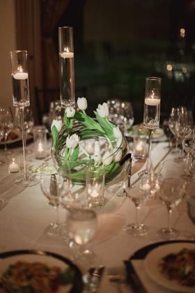 white tulips swirled in a glass bowl as modern wedding reception centerpiece