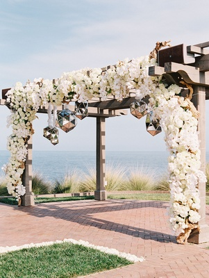 wooden arch oceanfront ceremony white flowers roses mirror balls reflective orbs shapes