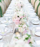 Wedding reception long farm table with pink, white flowers and table runner