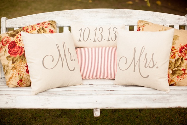 Floral pillows and wedding date pillow on bench
