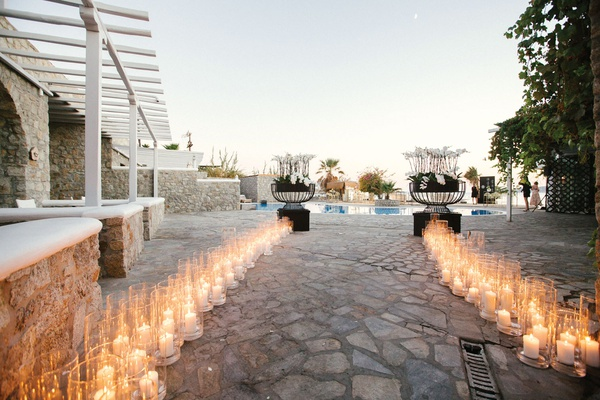 weddinng reception entrance pool and pillar candles in glass hurricanes white flowers black modern