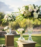 Desert wedding ceremony with oak riser pedestal glass vases white hydrangea, pink rose, greenery