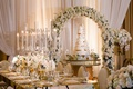 Wedding cake sugar flowers under flower arch long table candelabra gold chairs white flowers