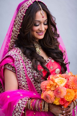Bride in fuchsia lehenga carrying yellow, orange, and red wedding bouquet rose, crysanthemum, orchid