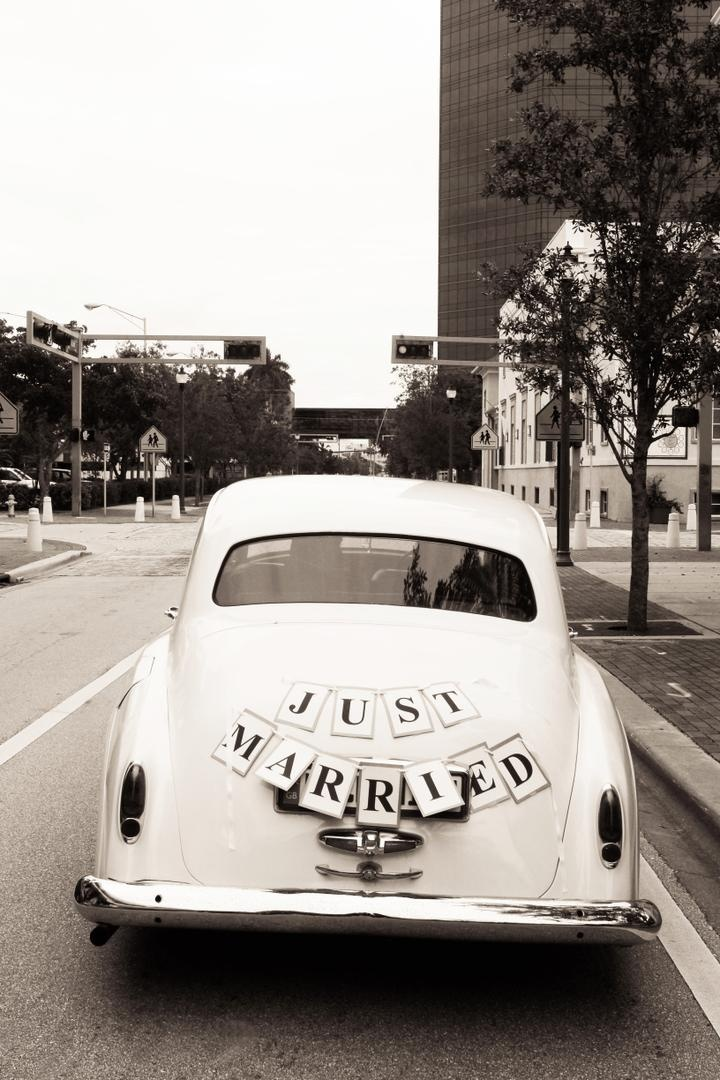 vintage white car with just married sign on back
