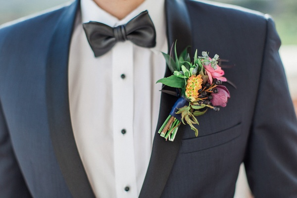 groom in navy tux with black lapel leather bow tie and boutonniere with colorful flowers