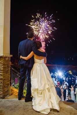 Bride and groom watch fireworks and their guests wedding reception surprise