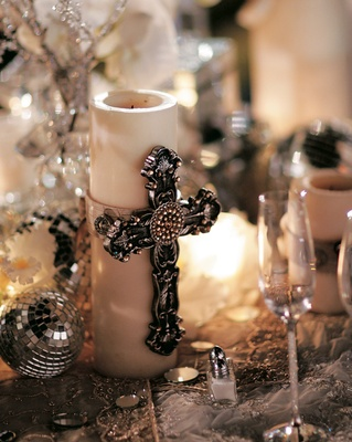 Reception centerpiece with silver Gothic cross on candle