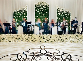 Live band performing on wedding stage decorated with greenery wall white rose flowers dance floor