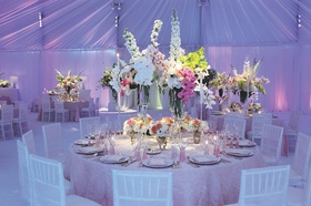 Reception table in white drapery room with orchid flowers