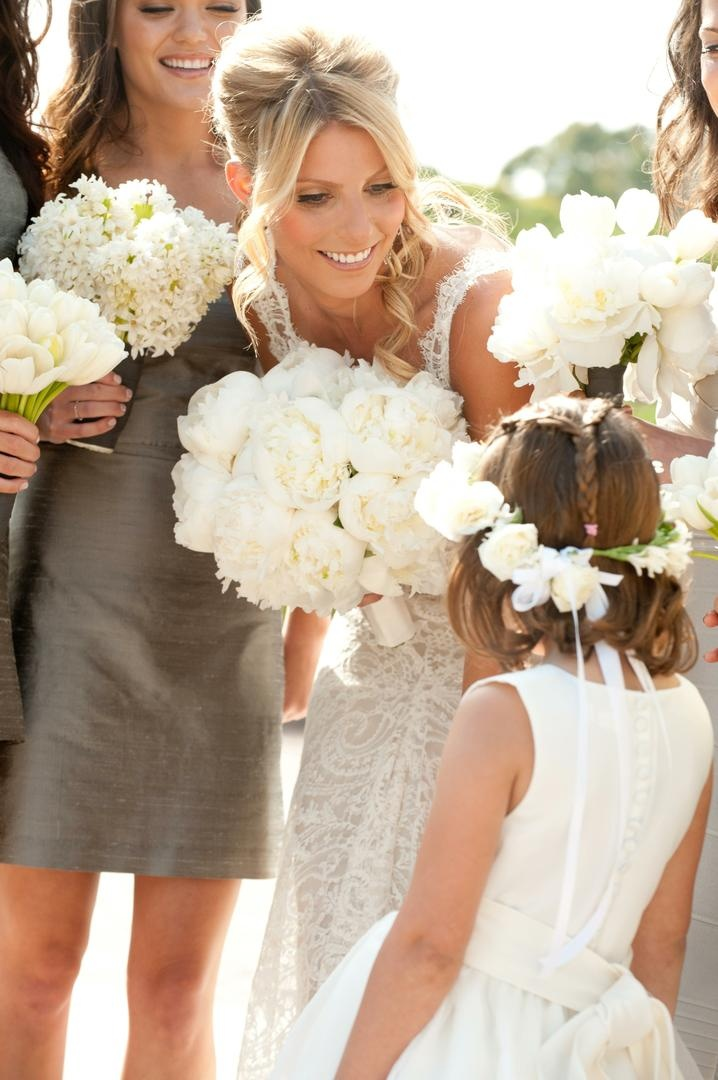 Bride leaning down to talk to cute young girl