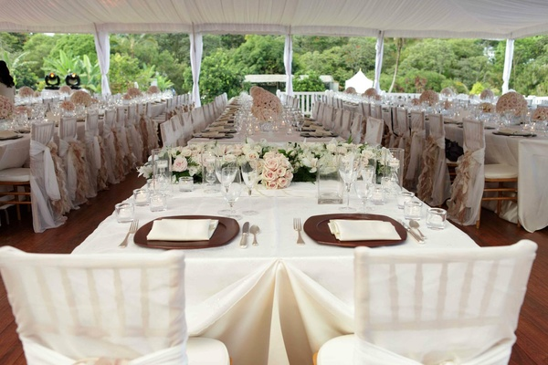 Wedding reception sweetheart table covered in white satin faces guest tables