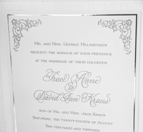 White paper invites with silver calligraphy and motif