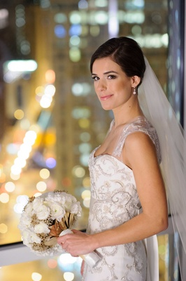 Bride in Monique Lhuillier wedding dress with white peony ranunculus bouquet gold leaves baby breath