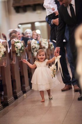 flower girl carrying floral wreath down catholic church aisle with one shoe