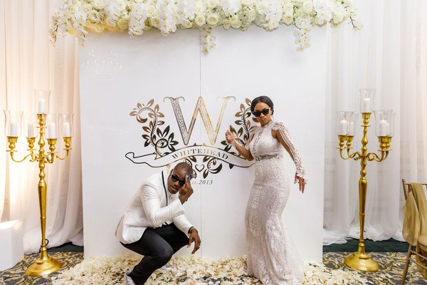 bride in second wedding dress groom in white tuxedo sun glasses monogram photo booth backdrop gold