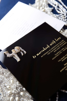 black and yellow invitations to a styled shoot with animal pendant on jewelry