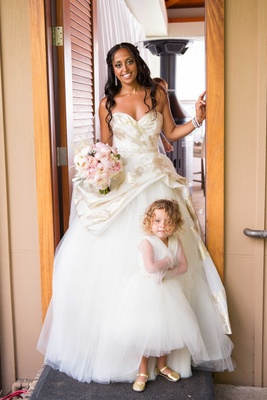 Chudney Ross in custom Lazaro wedding dress with daughter Callaway in flower girl dress gold flats