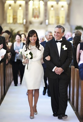 Mother of groom wearing ivory short dress with silver high heels and father of groom in tuxedo
