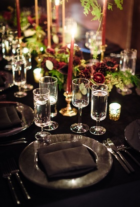 Black linen tablecloth black charger plate black napkin crystal glassware gold candleholder greenery