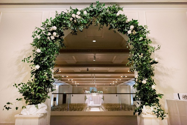 entrance to wedding ceremony with arch of greenery and a few white flowers