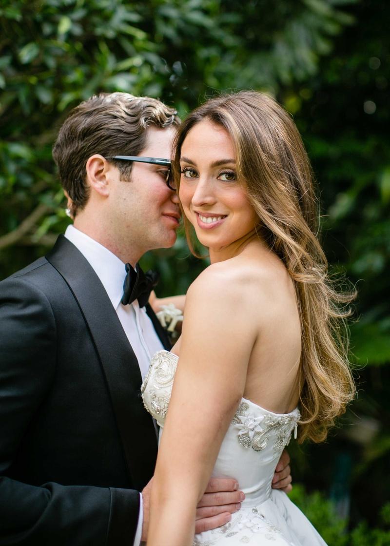 Groom in Tom Ford tuxedo bow tie glasses holds bride in strapless Oscar de la Renta wedding dress