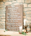 Wooden rehearsal dinner menu against wall