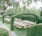 Long wood reception tables under green arches