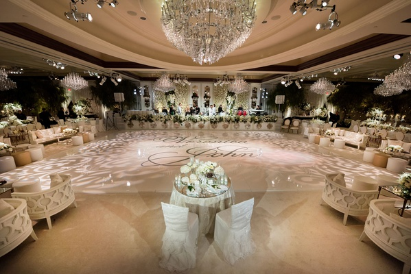 sweetheart table in front of large white dance floor lighting projections names on dance floor