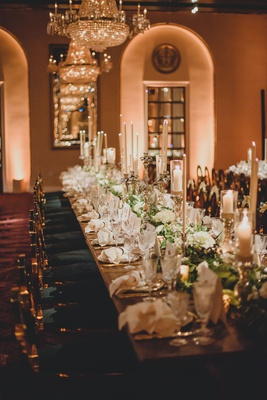 wedding reception long table green gold chairs taper candles chandelier white flowers greenery luxe