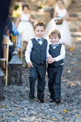 ring bearers in grey vets and blue bow ties hold hands while walking down the aisle