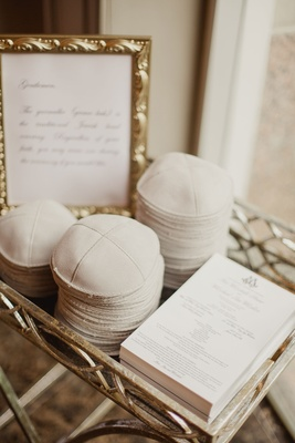 Wedding ceremony program and yarmulkes with sign in gold frame in tray at wedding ceremony Jewish
