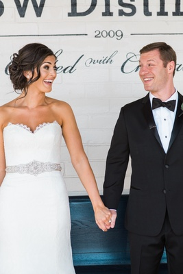 bride and groom hold hands and smile at each other in white dress and tuxedo