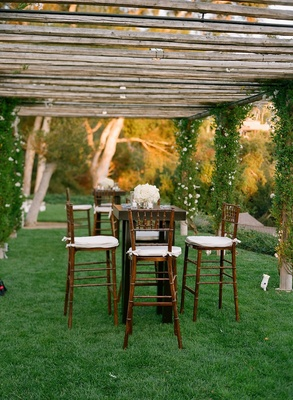 Tall cocktail table with wood chairs and white flowers