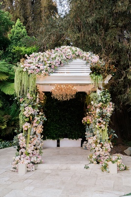 Greenery spilling from arch at Hotel Bel-Air wedding with pink roses chandelier garden venue
