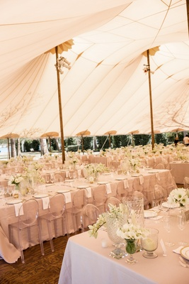 Tent wedding reception with long tables tan linens white napkins flowers clear ghost chairs