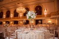 Wedding reception with golden chairs, embroidered overlays on tables, tall stand with white hydrange
