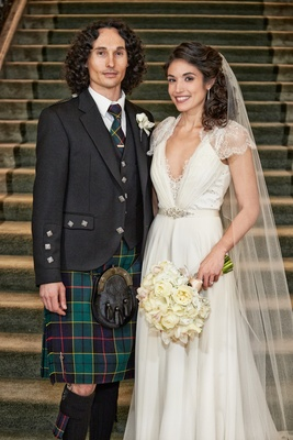 Bride in a Jenny Packham dress with lace details, veil, groom in green kilt, tie, blazer with studs