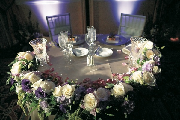 Bride and groom table with amaranthus, white roses, and lavender flowers and crystal