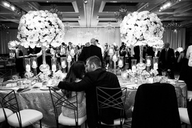 Black and white photo of bride and groom kissing at head table guests on dance floor