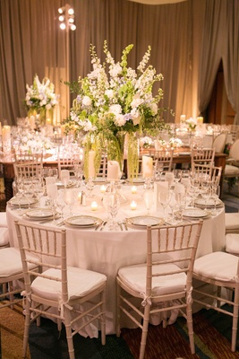 White dinner furniture topped with tall centerpiece