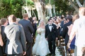Bride in a strapless Hayley Paige dress, beaded belt, tiered skirt walks up aisle with groom