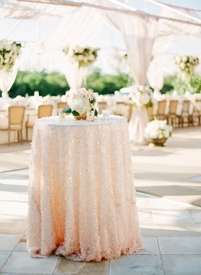 Garden wedding reception with an accent table with a sequined pink and white tablecloth and flowers