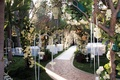 Outdoor garden wedding with flower arches and trees