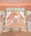 ivory, blush, peach flower arrangements on white stands and ceremony altar, peach uplighting